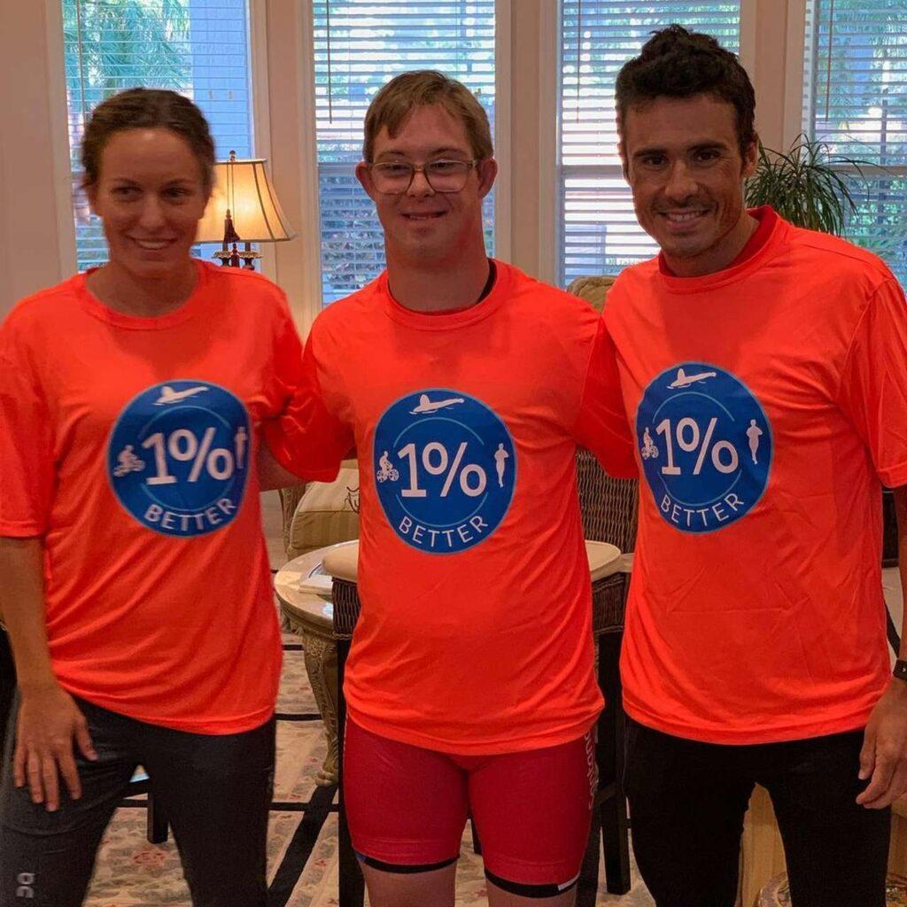 """Chris Nikic insieme ad Javier Gomez e sua moglie Anneke Jenkins con la maglia del progetto """"migliora ogni giorno dell'1 per cento"""""""